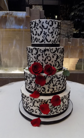 4 Tier Buttercream Wedding Cake Iced In Vanilla Decorated With Black Scrolls Fresh Red Stem Roses Rose Petals