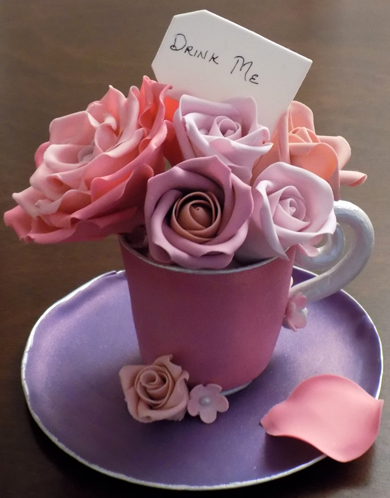 Custom handmade gumpaste tea cup and saucer with different shades of pink sugar roses