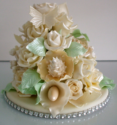Back view of hand made wedding cake topper of assorted off white flowers