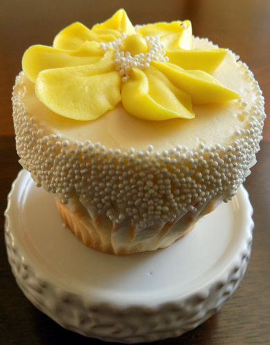 Lemon cupcakes, filled with raspberry filling, iced with lemon buttercream and decorated with white non perils and yellow buttercream flowers
