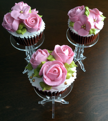 Red velvet cupcakes filled with cream cheese icing, iced with vanilla buttercream and decorated with pink buttercream roses and blossom flowers