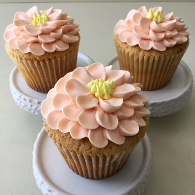 Cupcakes decorated with peach and yellow buttercream flowers