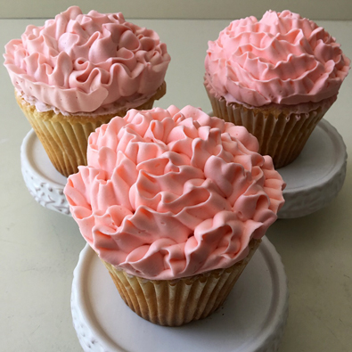 Cupcakes decorated with ruffle coral buttercream flowers
