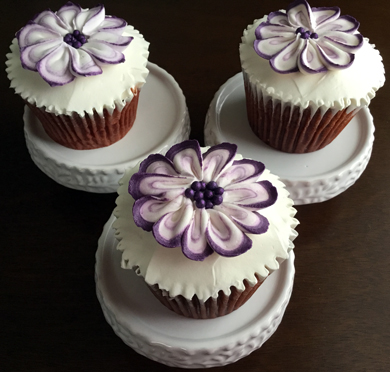 Red velvet cupcakes, filled with cream cheese icing, iced with vanilla buttercream and decorated with purple and white buttercream flowers delivered at Acorn Meadows in Thomasville PA