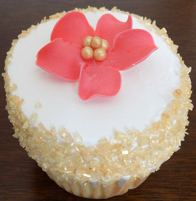 Yellow cupcakes, filled and iced with vanilla buttercream and decorated with gold sugar crystals and a gumpaste coral flower with a gold center