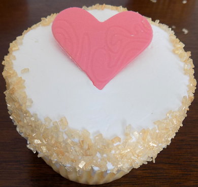 Yellow cupcakes filled and iced with vanilla buttercream, decorated with gold sugar crystals and a coral heart placque