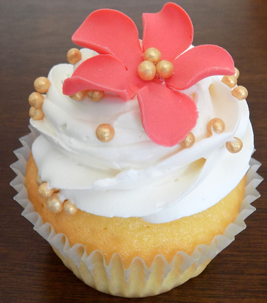 Yellow cupcakes filled and iced with a swirl of vanilla buttercream, decorated with gold  dragees and a coral gumpaste flower