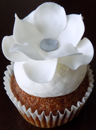 Carrot cupcakes, filled with cream cheese icing, topped with vanilla buttercream and decorated with a gumpaste flower with a diamond center