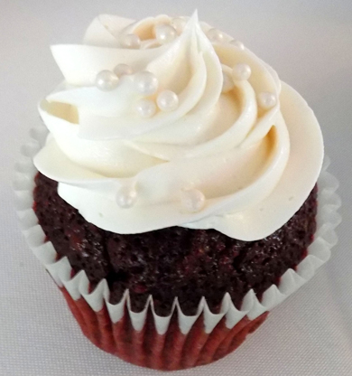Red velvet cupcake filled with cream cheese icing and topped with a swirl of vanilla buttercream icing and decorated with sugar pearl dragees. Cupcakes York PA