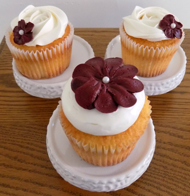 Orange cupcakes, filled with lemon buttercream, iced with vanilla buttercream, decorated with deep red buttercream flowers delivered at Red Lion PA Social Hall
