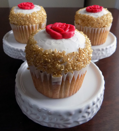 Banana cupcakes, filled with chocolate buttercream, topped with vanilla buttercream and decorated with gold sugar crystals and red fondant roses