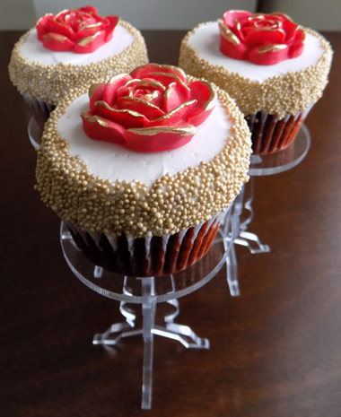 Red velvet cupcakes, filled with cream cheese icing, iced with vanilla buttercream and decorated with gold non-perils and red fondant roses with the edges painted in gold