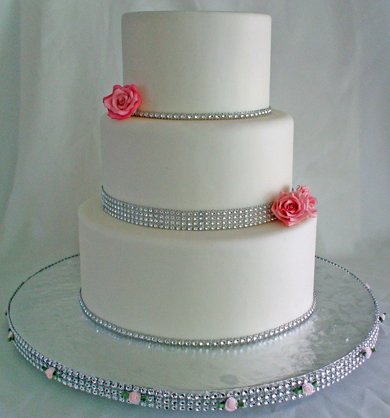 3 Tier Round White Fondant Wedding Cake Decorated With Bling Diamond Ribbons And Pink Sugar Flowers