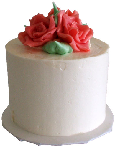 2 Inch round mini wedding cake, iced in vanilla buttercream and decorated with chocolate flowers