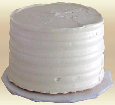 2 Inch round mini wedding cake, iced in vanilla buttercream and decorative combed sides